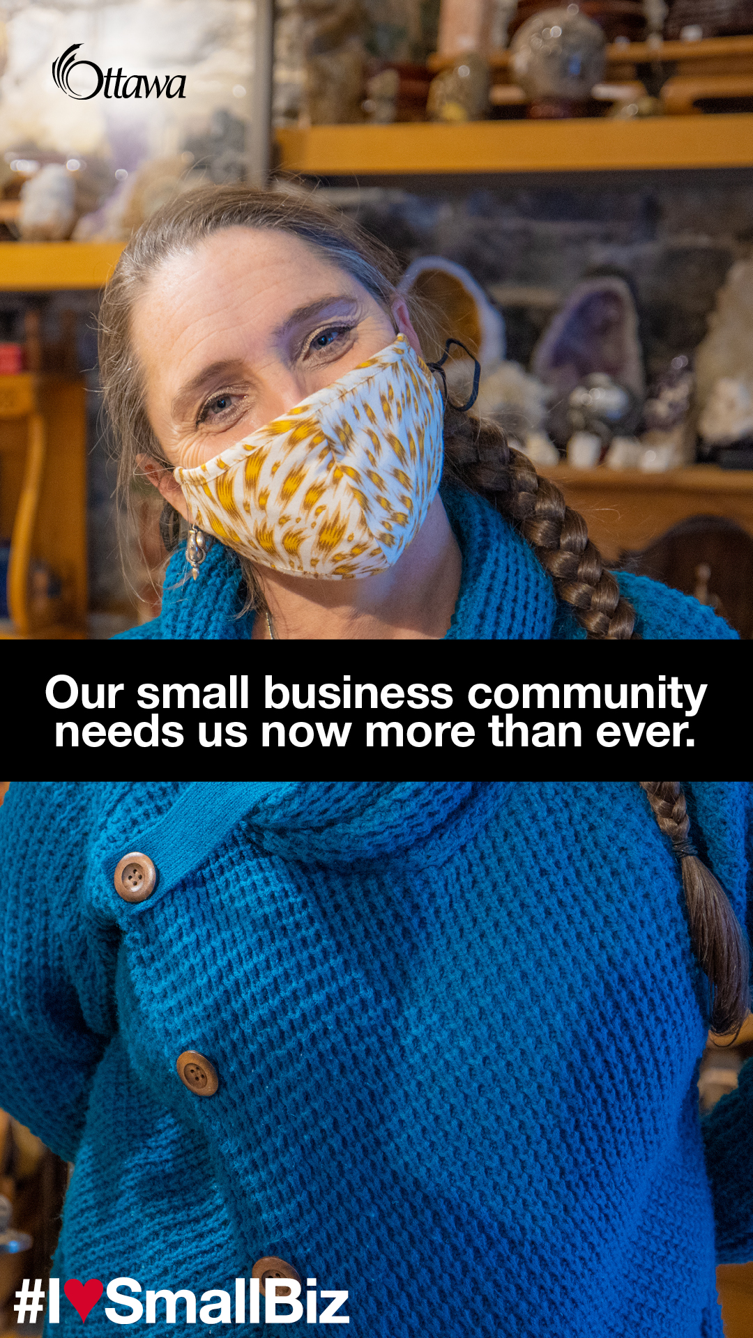 •	A woman wearing a mask stands in a small retail store. Our small business community needs us now more than ever.