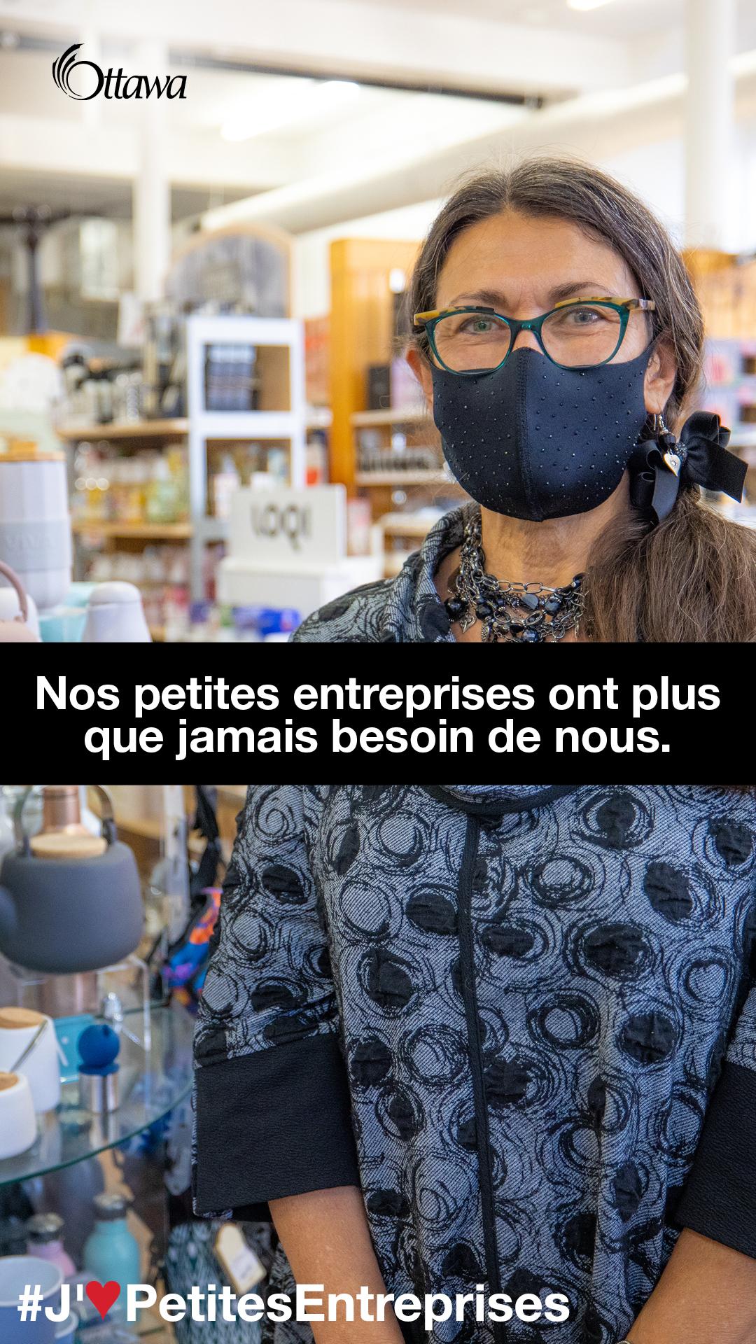 •Une femme qui porte un masque se trouve dans un petit magasin de détail. Nos petites entreprises ont plus que jamais besoin de nous.