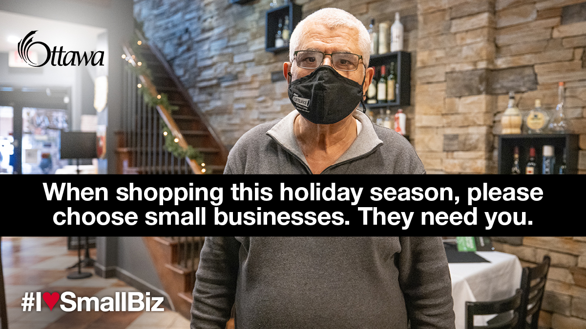 •	A man wearing a mask stands in a restaurant. When shopping this holiday season, please choose small businesses. They need you.