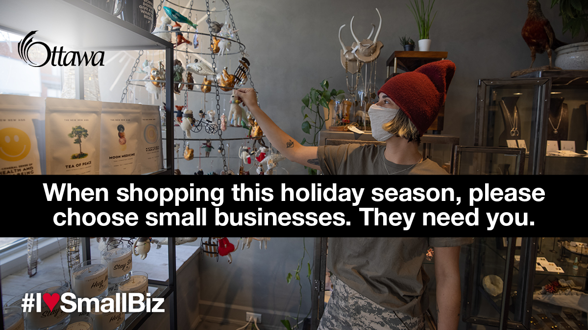 •	A woman wearing a mask stands in a gift shop. When shopping this holiday season, please choose small businesses. They need you.