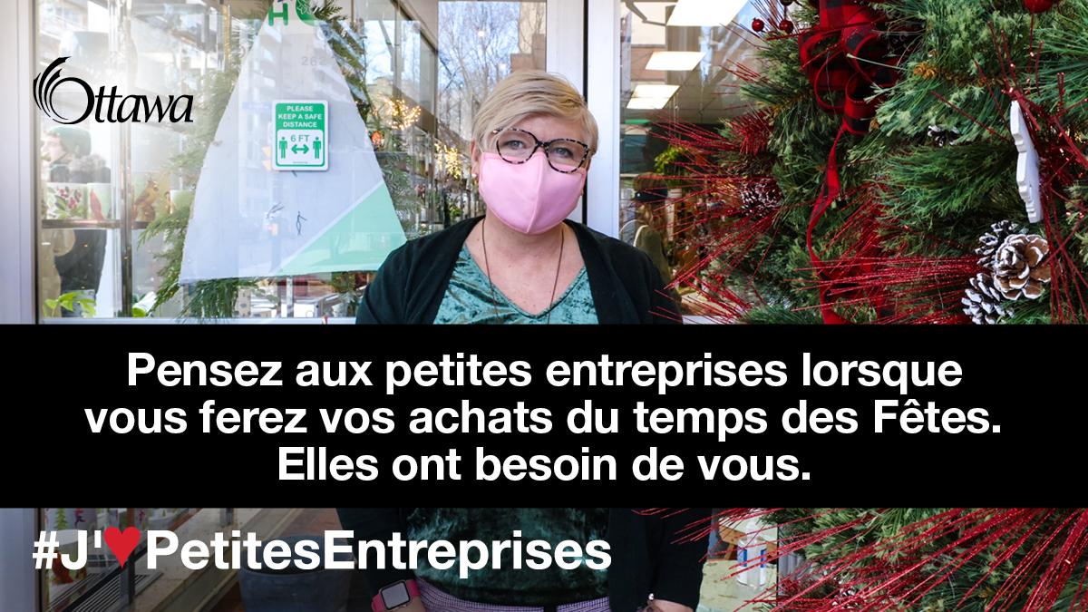 •Une femme qui porte un masque est à l'extérieur à côté d'une couronne des Fêtes. Pensez aux petites entreprises lorsque vous ferez vos achats du temps des Fêtes. Elles ont besoin de vous.