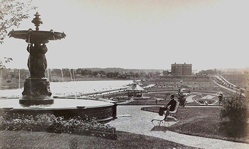 This historic photograph depicts a man sitting on a bench on the north end of Strathcona Park. The fountain is in the foreground, Rideau River off on the left and an apartment building in the background.