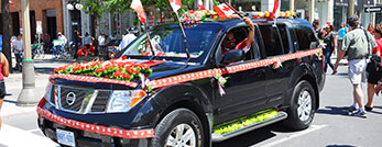 A man driving a car decorated to celebrate Canada Day