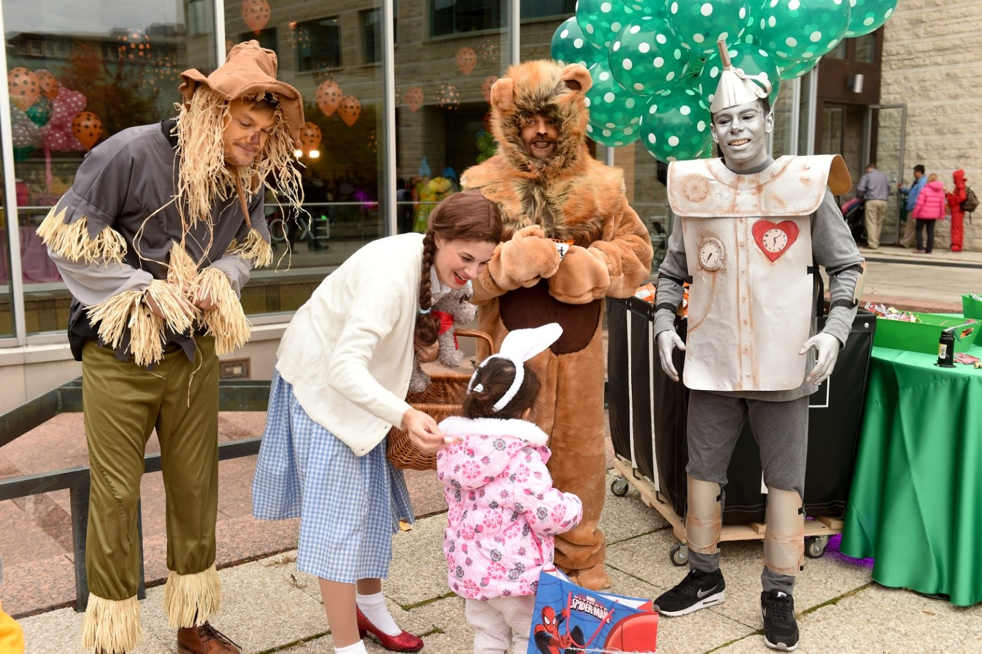 Wizard of Oz characters handing candy to child